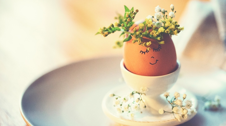 Ein Ei im Eierbecher mit aufgemaltem Gesicht und aufgesetztem Blütenkranz.