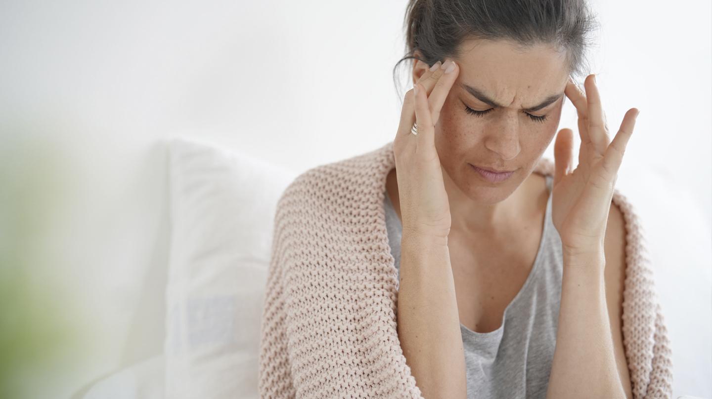 Kopfschmerz: Frau fasst sich an die Schläfen.